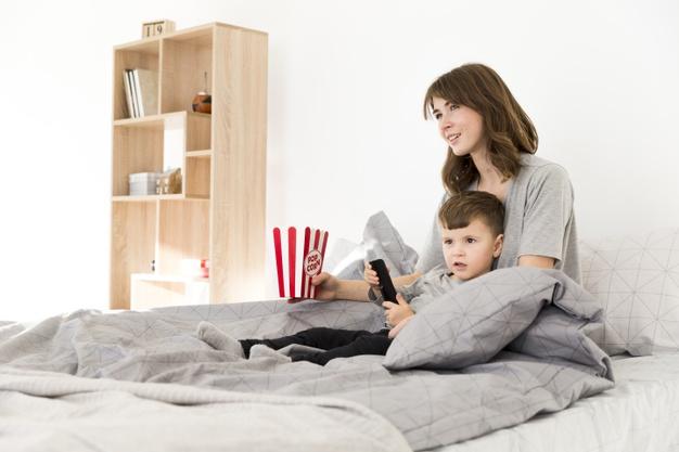 Madre e hijo cama viendo tv_23 2148443191