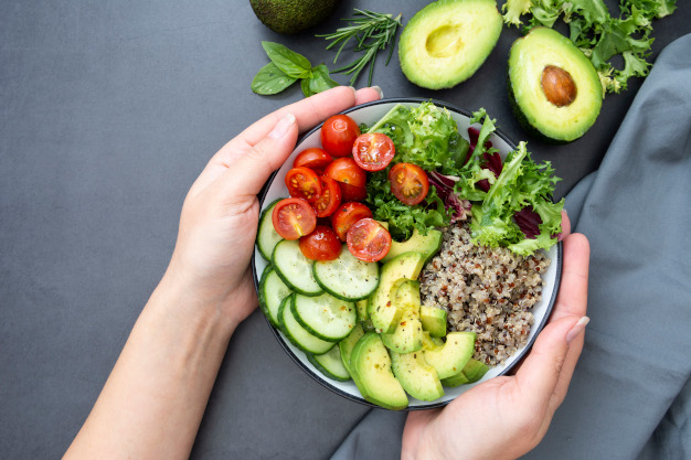 Healthy food. Womans hand holding budha bowl with quinoa, avocado, cucumber, salad, tomatoe, olive oil. Clean eating, diet food. Lose weight. Dark background.